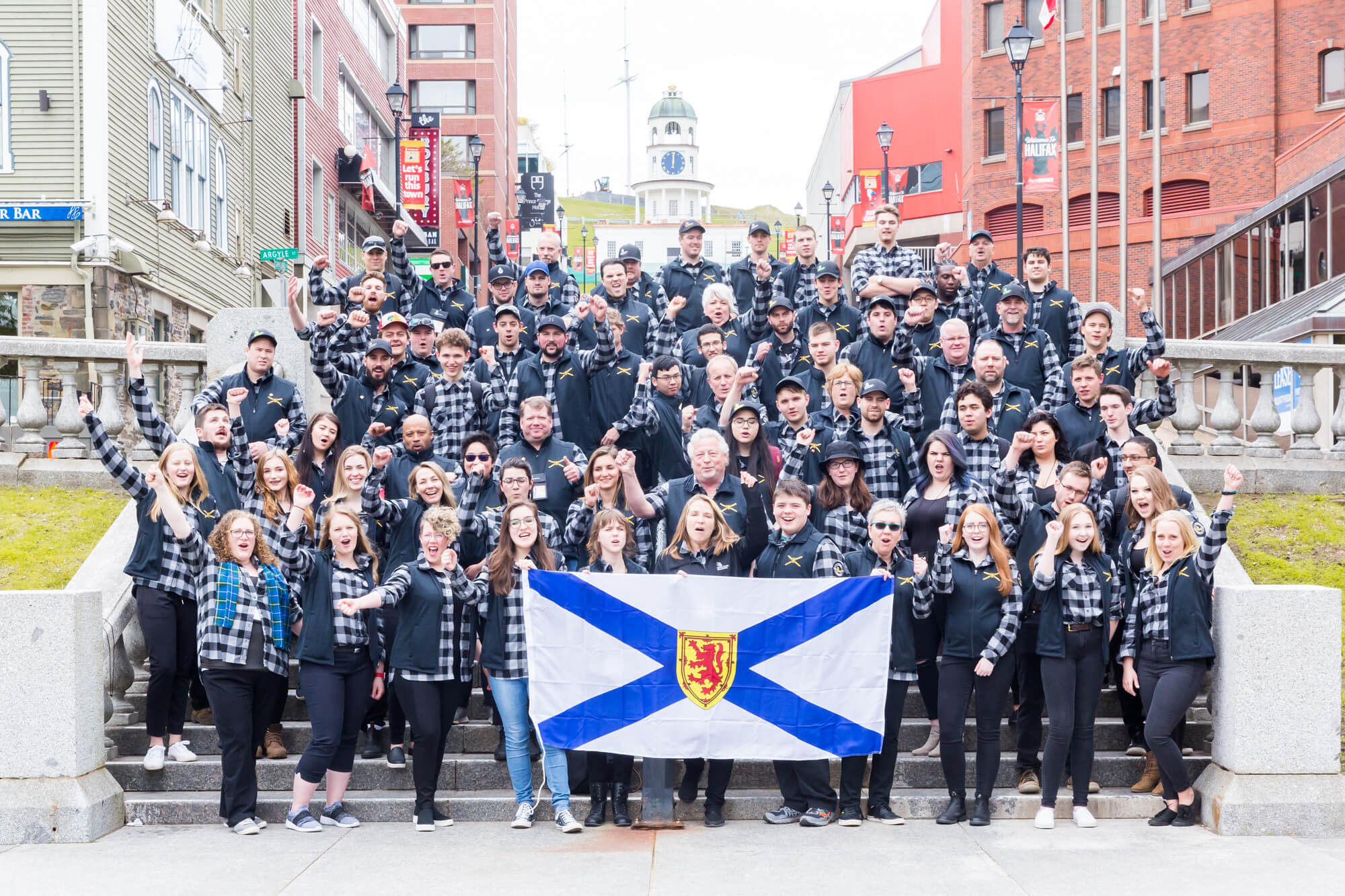 Group photo of the large team holding a Nova Scotia Flag